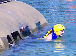 Student bailing out of a partially submerged helecopter in a lake.