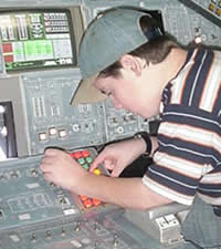 Student on the Shuttle Flight Deck entering commands into the Shuttle's computer.