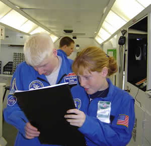 Student on the Space Station review a large print checklist.